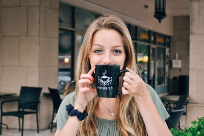 Young Blonde Woman Sipping Coffee from a Mug